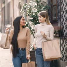 cheerful-friends-carrying-shopping-bags-and-smiling-3865911
